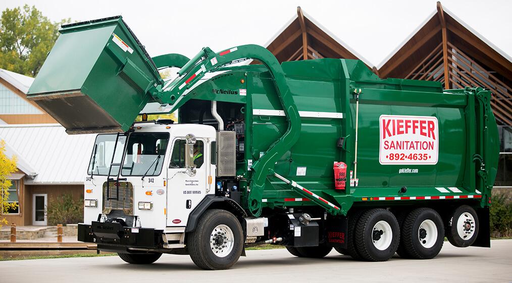 Photo of Kieffer sanitation truck lifting a commercial bin for dumping.