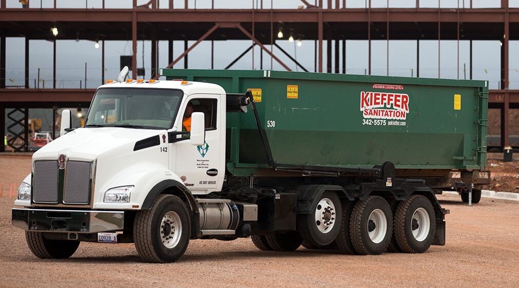 Photo of a Kieffer Sanitation truck with a roll-off bin ready for delivery.
