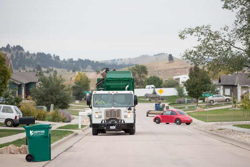 Picture of Kieffer Sanitation truck dumping 96 gallon carts in residential neighborhood.